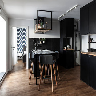 Design ideas for a small contemporary galley open plan kitchen in Other with black cabinets, tile benchtops, black splashback, medium hardwood floors, a peninsula, brown floor and multi-coloured benchtop.