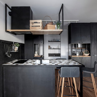 Design ideas for a small contemporary galley open plan kitchen in Other with an undermount sink, flat-panel cabinets, black cabinets, black splashback, medium hardwood floors and a peninsula.