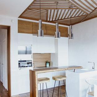 Свежая идея для дизайна: параллельная кухня в современном стиле с обеденным столом, плоскими фасадами, белыми фасадами, коричневым фартуком, паркетным полом среднего тона, полуостровом и коричневым полом - отличное фото интерьера