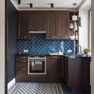 На фото: маленькая угловая кухня в современном стиле с одинарной раковиной, темными деревянными фасадами, столешницей из акрилового камня, фартуком из керамической плитки, техникой из нержавеющей стали, полом из керамической плитки, синим полом, фасадами с утопленной филенкой, синим фартуком и черной столешницей без острова