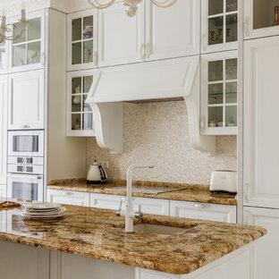 На фото: кухня в стиле современная классика с врезной раковиной, фасадами с выступающей филенкой, белыми фасадами, бежевым фартуком, фартуком из плитки мозаики, белой техникой, островом и коричневой столешницей