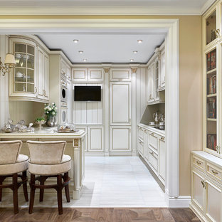 Пример оригинального дизайна: п-образная кухня-гостиная в классическом стиле с монолитной раковиной, белыми фасадами, столешницей из кварцевого агломерата, бежевым фартуком, фартуком из дерева, белой техникой, полом из керамогранита, полуостровом, белым полом и фасадами с утопленной филенкой