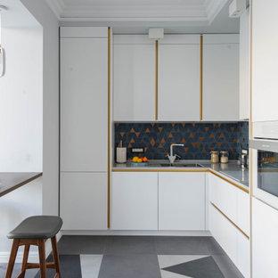 На фото: большая угловая кухня в скандинавском стиле с обеденным столом, врезной раковиной, плоскими фасадами, белыми фасадами, столешницей из акрилового камня, разноцветным фартуком, фартуком из керамической плитки, белой техникой, полом из керамической плитки, серым полом, серой столешницей и многоуровневым потолком без острова