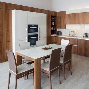Новые идеи обустройства дома: угловая кухня в стиле модернизм с врезной раковиной, плоскими фасадами, фасадами цвета дерева среднего тона, белым фартуком, серым полом, обеденным столом и черной техникой без острова