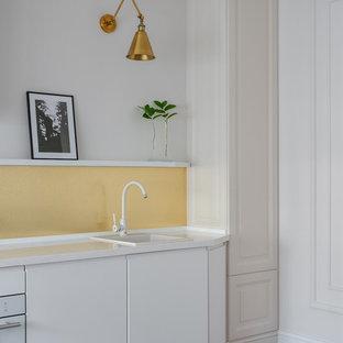Идея дизайна: линейная кухня в современном стиле с накладной раковиной, плоскими фасадами, белыми фасадами, желтым фартуком, белой техникой, коричневым полом, белой столешницей и паркетным полом среднего тона