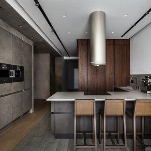 На фото: п-образная кухня-гостиная в современном стиле с врезной раковиной, плоскими фасадами, серым фартуком, черной техникой, полуостровом, серым полом, столешницей из бетона и фартуком из цементной плитки с