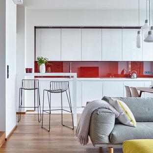 Свежая идея для дизайна: линейная кухня-гостиная в скандинавском стиле с плоскими фасадами, белыми фасадами, столешницей из акрилового камня, красным фартуком, фартуком из стекла, белой техникой, полом из керамогранита и белым полом без острова - отличное фото интерьера
