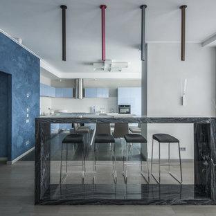 Неиссякаемый источник вдохновения для домашнего уюта: кухня-гостиная среднего размера в современном стиле с столешницей из гранита, полом из керамогранита, серым полом, серой столешницей, плоскими фасадами, синими фасадами и серым фартуком без острова
