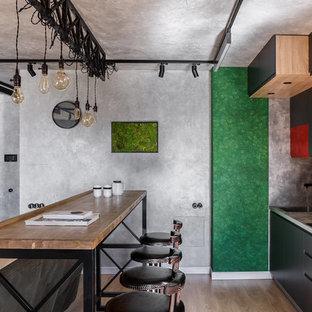 На фото: маленькая прямая кухня-гостиная в современном стиле с плоскими фасадами, черными фасадами, серым фартуком, светлым паркетным полом, бежевым полом, серой столешницей, одинарной раковиной и островом