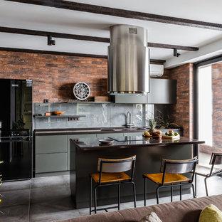 他の地域の中サイズのインダストリアルスタイルのおしゃれなキッチン (フラットパネル扉のキャビネット、グレーのキャビネット、人工大理石カウンター、グレーのキッチンパネル、ガラス板のキッチンパネル、磁器タイルの床、グレーの床、黒いキッチンカウンター) の写真