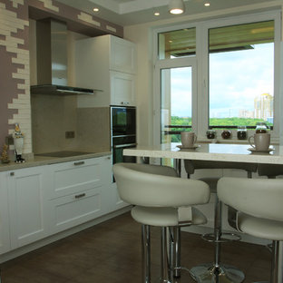 Inspiration for a large contemporary l-shaped separate kitchen in Moscow with an undermount sink, raised-panel cabinets, white cabinets, solid surface benchtops, beige splashback, slate splashback, porcelain floors, with island, green floor and beige benchtop.