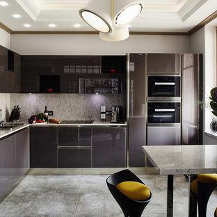 На фото: угловая кухня в современном стиле с накладной раковиной, плоскими фасадами, разноцветным фартуком, черной техникой, полуостровом и серым полом