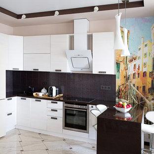 Создайте стильный интерьер: п-образная кухня-гостиная в современном стиле с плоскими фасадами, белыми фасадами, черным фартуком, техникой из нержавеющей стали и полуостровом - последний тренд