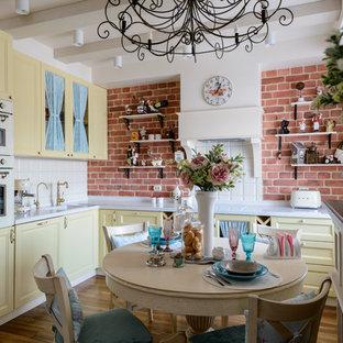 Inspiration för ett industriellt kök, med gula skåp och stänkskydd i tegel