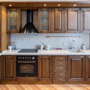 Свежая идея для дизайна: угловая кухня среднего размера в классическом стиле с монолитной раковиной, фасадами с выступающей филенкой, фасадами цвета дерева среднего тона, серым фартуком, фартуком из керамогранитной плитки, черной техникой, полуостровом, бежевым полом и белой столешницей - отличное фото интерьера
