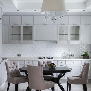 Выдающиеся фото от архитекторов и дизайнеров интерьера: кухня - столовая в стиле современная классика с белым фартуком, фартуком из плитки кабанчик, стеклянными фасадами и серыми фасадами без острова