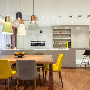Пример оригинального дизайна: параллельная кухня в современном стиле с обеденным столом, плоскими фасадами, белыми фасадами, черной техникой, белым полом и белой столешницей