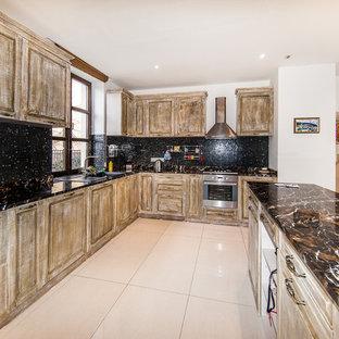 モスクワのシャビーシック調のおしゃれなキッチン (レイズドパネル扉のキャビネット、ヴィンテージ仕上げキャビネット、黒いキッチンパネル、モザイクタイルのキッチンパネル、シルバーの調理設備の) の写真
