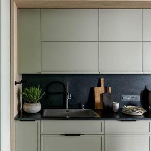 Idéer för att renovera ett avskilt, mellanstort funkis svart svart parallellkök, med en undermonterad diskho, släta luckor, gröna skåp, granitbänkskiva, svart stänkskydd, stänkskydd i sten, rostfria vitvaror, terrazzogolv, en köksö och vitt golv