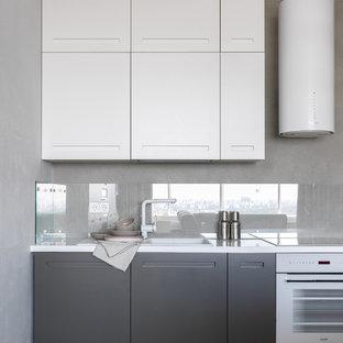 Новый формат декора квартиры: кухня среднего размера в современном стиле с накладной раковиной, плоскими фасадами, фартуком из стекла, белой техникой, полом из керамической плитки, белой столешницей, серыми фасадами, серым фартуком и серым полом