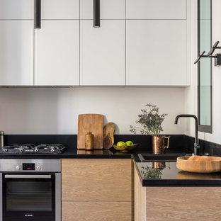 Пример оригинального дизайна интерьера: маленькая угловая кухня-гостиная в скандинавском стиле с плоскими фасадами, белыми фасадами, черным фартуком, техникой из нержавеющей стали, черной столешницей, столешницей из акрилового камня, фартуком из каменной плиты и накладной раковиной без острова