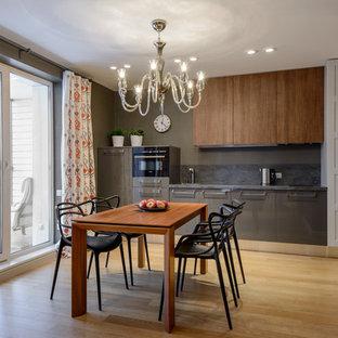 Свежая идея для дизайна: линейная кухня-гостиная в современном стиле с плоскими фасадами, серым фартуком, черной техникой и светлым паркетным полом без острова - отличное фото интерьера