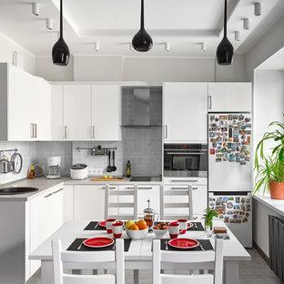Пример оригинального дизайна: угловая кухня в скандинавском стиле с обеденным столом, накладной раковиной, плоскими фасадами, белыми фасадами, серым фартуком, черной техникой, серым полом и белой столешницей