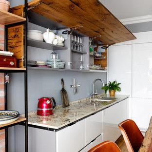 Стильный дизайн: кухня среднего размера в современном стиле с врезной раковиной, плоскими фасадами, белыми фасадами, серым фартуком, паркетным полом среднего тона и разноцветной столешницей - последний тренд