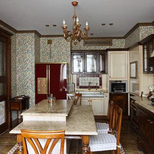 На фото: отдельная, угловая кухня в викторианском стиле с раковиной в стиле кантри, темными деревянными фасадами, бежевым фартуком, техникой из нержавеющей стали, островом, коричневым полом и бежевой столешницей с