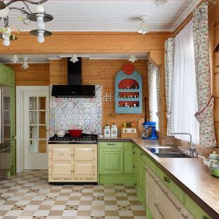 Идея дизайна: большая угловая кухня в стиле кантри с обеденным столом, фасадами с выступающей филенкой, зелеными фасадами, столешницей из ламината, разноцветным фартуком, фартуком из керамической плитки, полом из керамической плитки, разноцветным полом, бежевой столешницей, накладной раковиной и цветной техникой без острова