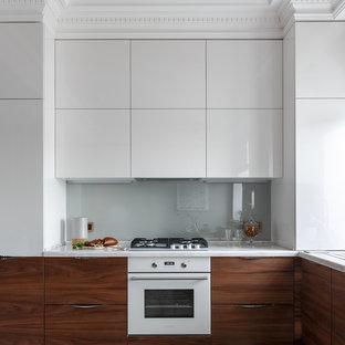 Новый формат декора квартиры: угловая кухня в современном стиле с плоскими фасадами, белыми фасадами, серым фартуком, фартуком из стекла, белой техникой, бежевым полом и белой столешницей