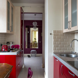 This is an example of a small contemporary galley separate kitchen in Moscow with flat-panel cabinets, red cabinets, solid surface benchtops, beige splashback, panelled appliances, porcelain floors, a drop-in sink, subway tile splashback, no island and white floor.