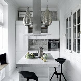 Стильный дизайн: линейная кухня в современном стиле с врезной раковиной, плоскими фасадами, белыми фасадами, серым фартуком, техникой из нержавеющей стали, островом, белым полом и серой столешницей - последний тренд