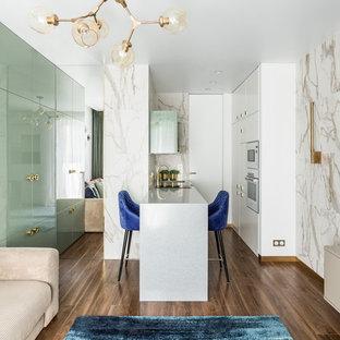 На фото: маленькая, узкая параллельная кухня-гостиная в современном стиле с плоскими фасадами, белыми фасадами, столешницей из акрилового камня, белым фартуком, фартуком из мрамора, белой техникой, полом из ламината, коричневым полом, серой столешницей, полуостровом и монолитной раковиной