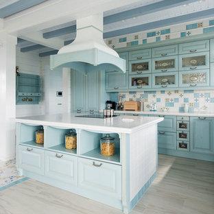На фото: угловая кухня-гостиная в средиземноморском стиле с накладной раковиной, фасадами с выступающей филенкой, бирюзовыми фасадами, столешницей из плитки, разноцветным фартуком, фартуком из керамической плитки, островом, бежевым полом и белой столешницей с