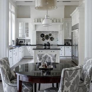 Пример оригинального дизайна: кухня в классическом стиле с обеденным столом, белыми фасадами, белым фартуком, фартуком из плитки кабанчик и островом