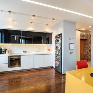 モスクワの小さいコンテンポラリースタイルのおしゃれなキッチン (一体型シンク、ガラス扉のキャビネット、黒いキャビネット、白いキッチンパネル、レンガのキッチンパネル、シルバーの調理設備、濃色無垢フローリング、アイランドなし) の写真