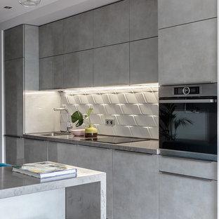Пример оригинального дизайна: линейная кухня среднего размера в современном стиле с белым фартуком, фартуком из керамической плитки, светлым паркетным полом, островом, серой столешницей, плоскими фасадами, серыми фасадами, техникой из нержавеющей стали, бежевым полом и одинарной раковиной