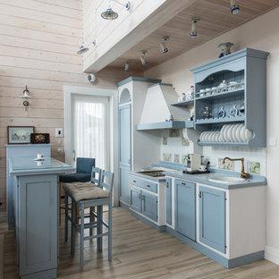 Lantlig inredning av ett linjärt kök med öppen planlösning, med blå skåp, kaklad bänkskiva, vitt stänkskydd, stänkskydd i keramik, klinkergolv i porslin, en nedsänkt diskho, luckor med infälld panel, en halv köksö och beiget golv