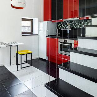 Свежая идея для дизайна: маленькая линейная кухня-гостиная в современном стиле с плоскими фасадами, красными фасадами, техникой из нержавеющей стали, разноцветным полом, черной столешницей, разноцветным фартуком и фартуком из плитки мозаики без острова - отличное фото интерьера