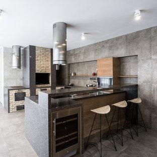Стильный дизайн: п-образная кухня в стиле лофт с плоскими фасадами, фасадами цвета дерева среднего тона, серым фартуком, техникой из нержавеющей стали, серым полом и серой столешницей - последний тренд