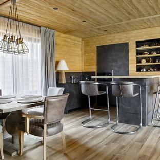 Стильный дизайн: кухня-гостиная в стиле рустика с плоскими фасадами, серыми фасадами, серым фартуком, светлым паркетным полом, островом, бежевым полом, черной столешницей и техникой под мебельный фасад - последний тренд