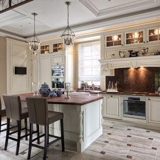 Новые идеи обустройства дома: угловая кухня в стиле современная классика с раковиной в стиле кантри, фасадами с выступающей филенкой, белыми фасадами, коричневым фартуком, техникой из нержавеющей стали, островом и серым полом