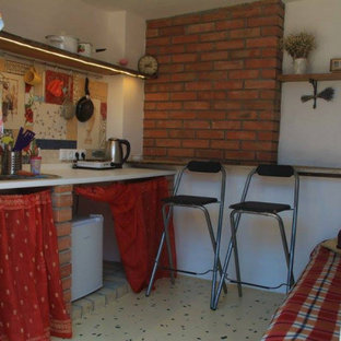 Small country single-wall separate kitchen in Other with an undermount sink, open cabinets, red cabinets, laminate benchtops, multi-coloured splashback, ceramic splashback, concrete floors, no island, yellow floor and white benchtop.