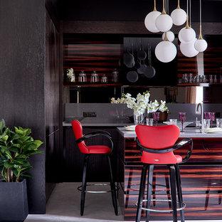 Идея дизайна: кухня-гостиная в современном стиле с плоскими фасадами, темными деревянными фасадами, серым фартуком, островом и серым полом