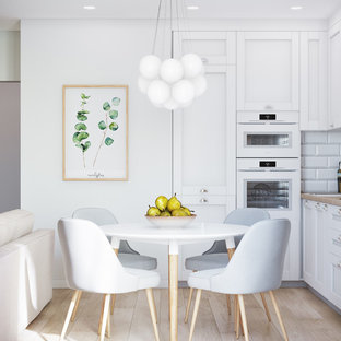 Inspiration for a small scandinavian l-shaped open plan kitchen in Other with beaded inset cabinets, white cabinets, a drop-in sink, wood benchtops, white splashback, ceramic splashback, white appliances, laminate floors, beige floor and beige benchtop.