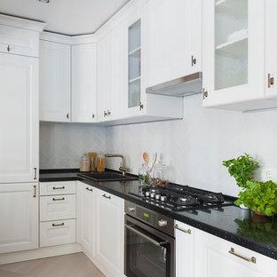 На фото: угловая, отдельная кухня в стиле современная классика с накладной раковиной, белыми фасадами, белым фартуком, техникой из нержавеющей стали, бежевым полом, черной столешницей и фасадами с выступающей филенкой без острова с