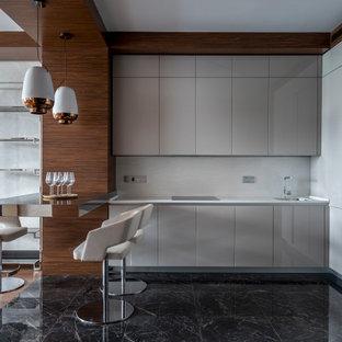 Стильный дизайн: угловая кухня среднего размера в современном стиле с врезной раковиной, плоскими фасадами, серыми фасадами, белым фартуком, техникой под мебельный фасад, полуостровом, черным полом и белой столешницей - последний тренд
