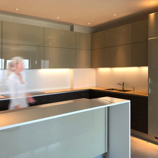 Inspiration for a large modern u-shaped eat-in kitchen in Other with a double-bowl sink, flat-panel cabinets, solid surface benchtops, white splashback, porcelain floors, with island, beige floor, beige cabinets, glass sheet splashback, black appliances and yellow benchtop.
