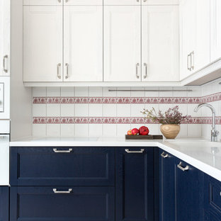Contemporary l-shaped kitchen in Moscow with an undermount sink, recessed-panel cabinets, blue cabinets, white splashback, white appliances, no island, beige floor and white benchtop.